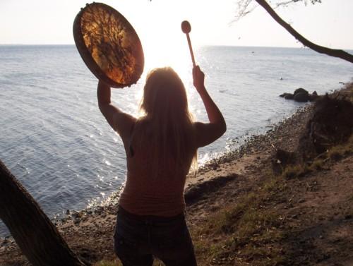 Susanne tanzt eines Morgens mit ihrer Schamanentrommel mit der Sonne